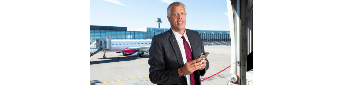 a man in a suit with Arlanda flight tower in the background