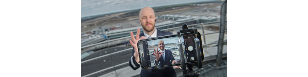A man in front of a camera lens and Arlanda airport in the background