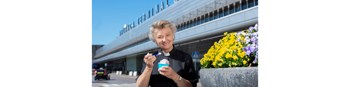 A female priest otuside a terminal at Arlanda eating ice cream