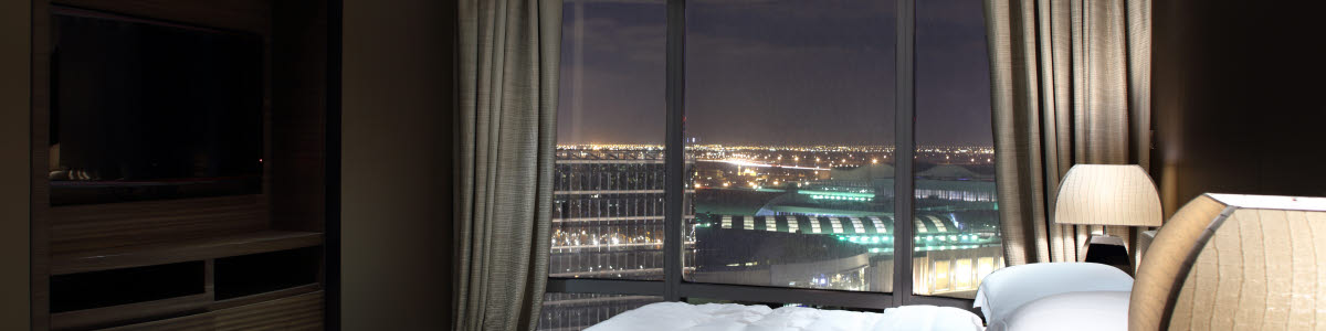 Hotel room with a bed and a view over a city