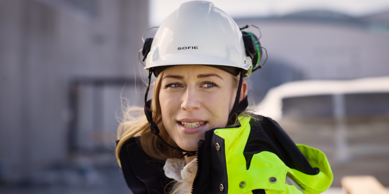 A woman in a construction helmet and a safety jacket