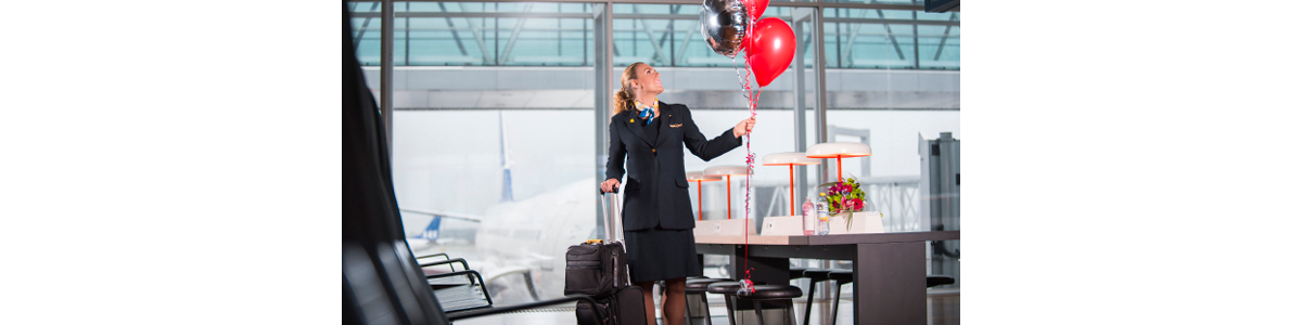 A flight attendant with suitcases and balloons
