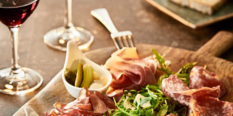 A plate with charcuterie and wine glasses