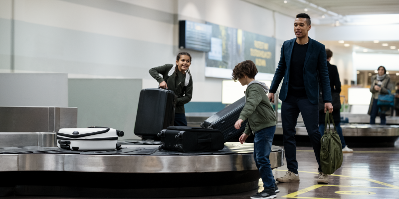 A man och two children at a baggage carousel