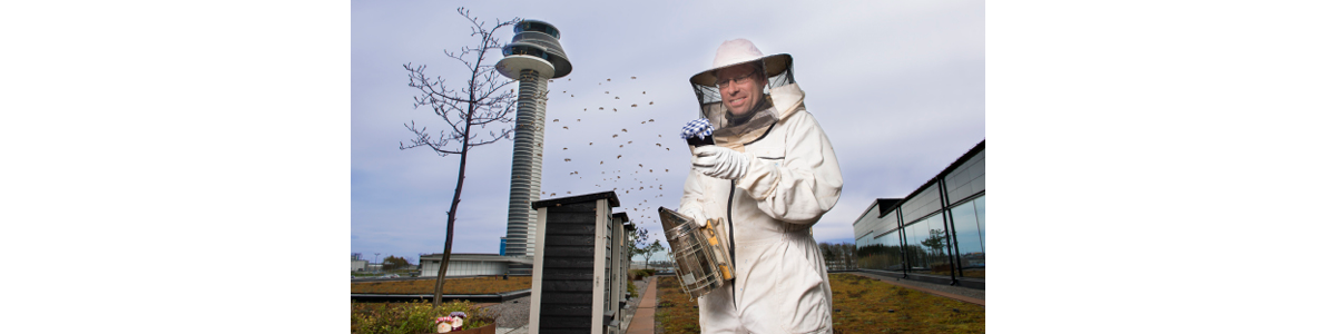 A man in a bee suit with Arlanda flight tower in the background