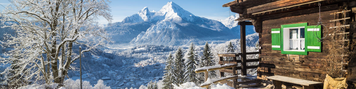 Panoramic view of scenic white winter wonderland mountain scenery in the Alps with traditional old wooden mountain chalets on a beautiful cold sunny day with blue sky and clouds