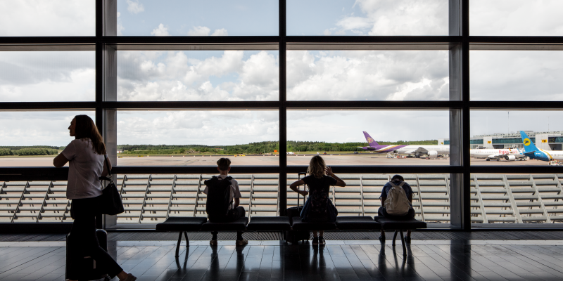 People at a window in SkyCity Arlanda overlooking aeroplanes at the runway