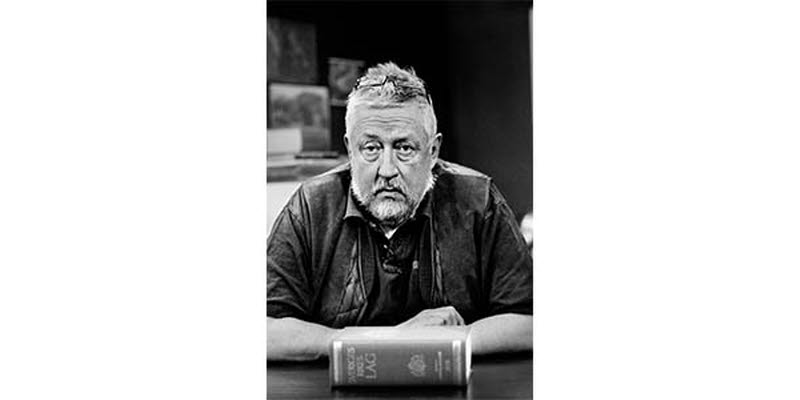 A photo of Leif GW Persson with the Swedish law book in front of him