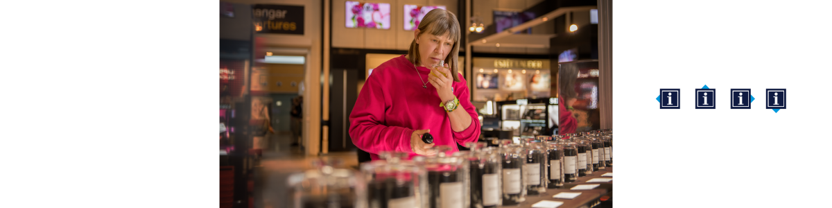 A woman in a pink sweater trying a perfume in a shop