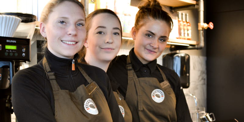 Three girls posing behind the counter at the Espresso house in Sky City