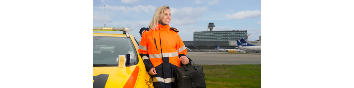 A woman in a visibility jacket at a yellow car sith Arlanda airport in the background