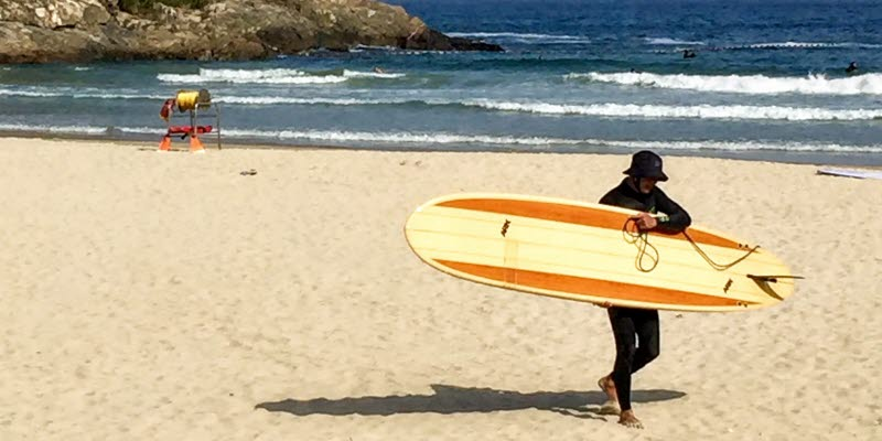 Man with surfboard on a beach